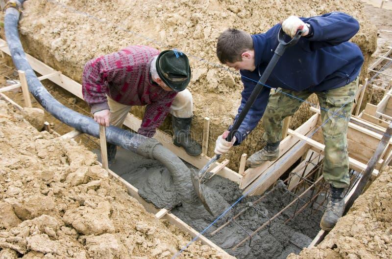 Construtores que fazem fundações imagens de stock
