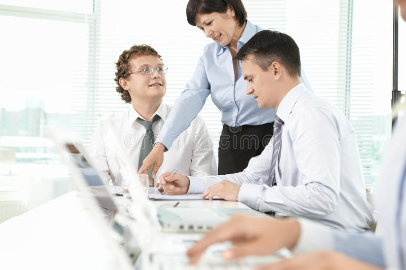 Consulation. Group of business partners listening to mature women explaining her idea at meeting royalty free stock photos