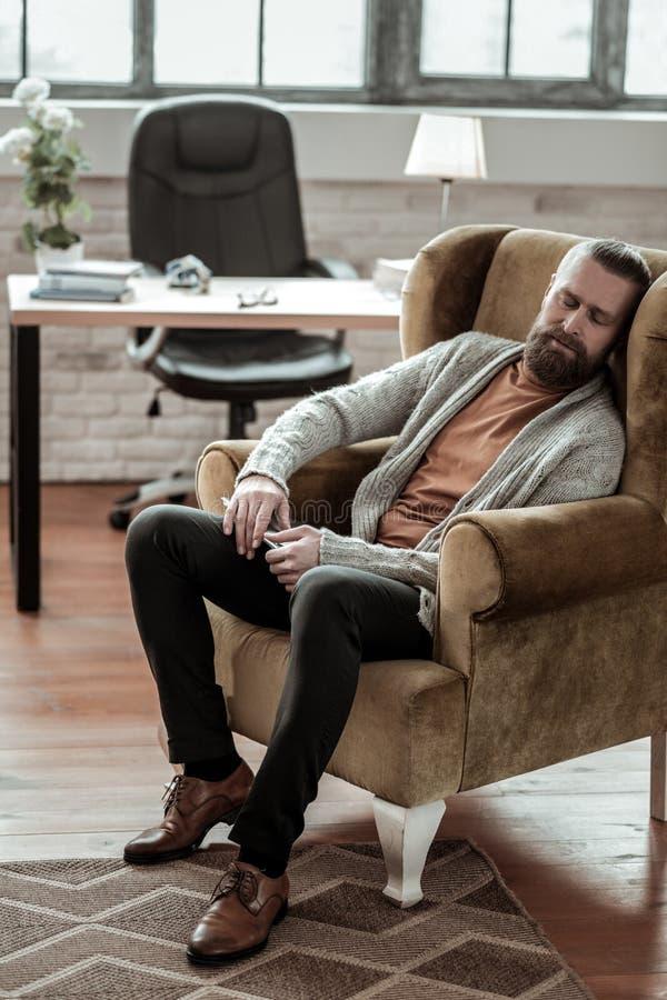 Consulente barbuto che indossa caduta grigia del cardigan addormentata immagini stock libere da diritti