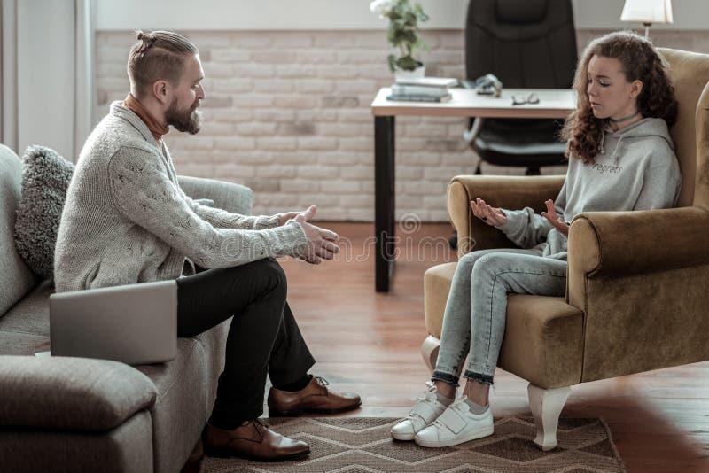 Consulente barbuto professionista che parla con l'adolescente fotografia stock