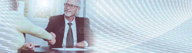 Consulente che stringe mano con il cliente dopo la firma del contratto, effetto della luce Bandiera panoramica fotografia stock libera da diritti