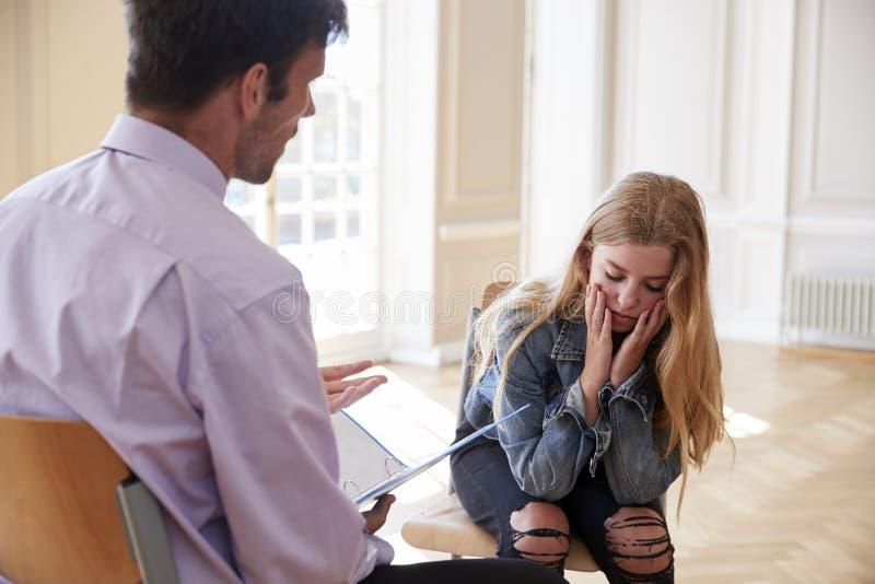Consulente della scuola che parla con allievo femminile depresso fotografia stock libera da diritti