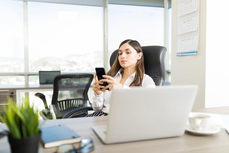 Consulente femminile Reading Emails On Smartphone in ufficio immagine stock libera da diritti