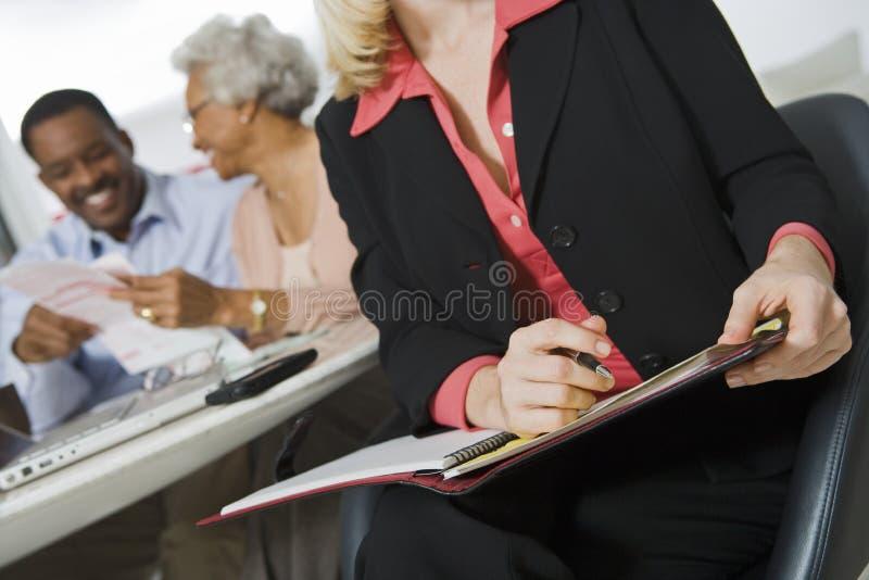 Consulente finanziario che assiste le coppie senior immagini stock