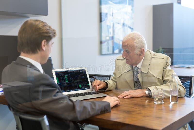 Consulente finanziario che consulta cliente senior con la sua strategia di investimento fotografia stock libera da diritti