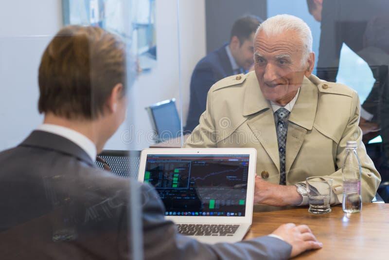 Consulente finanziario che consulta cliente senior con la sua strategia di investimento fotografia stock