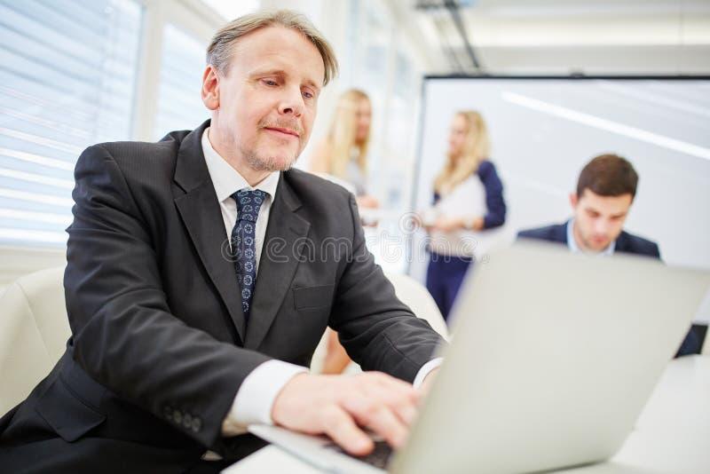 Consulente in materia dell'uomo con il computer portatile immagine stock