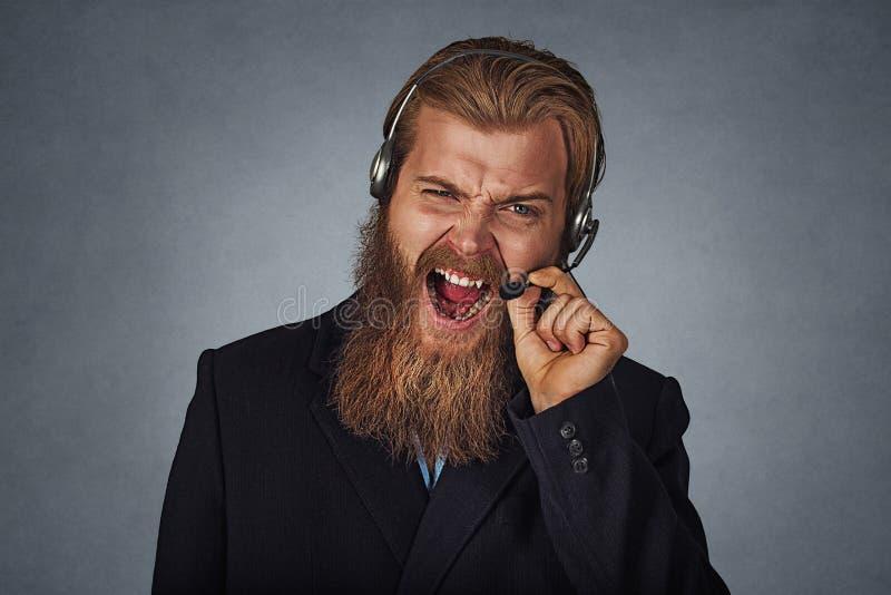 Consulente in materia dell'uomo della call center che grida esasperato immagine stock libera da diritti