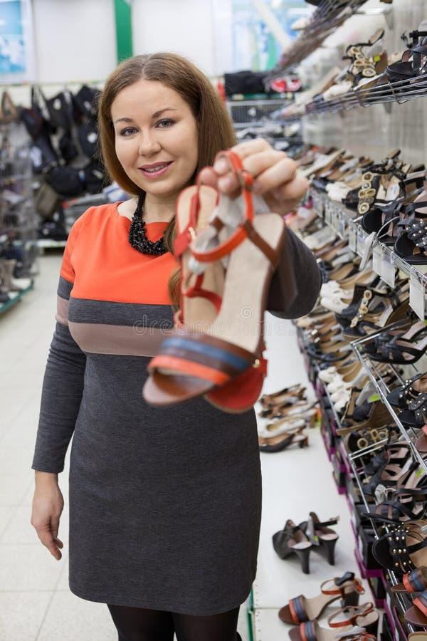 Consulente in materia femminile attraente del in-deposito che mostra le pantofole scalze Giudicando le scarpe smussate disponibil fotografia stock