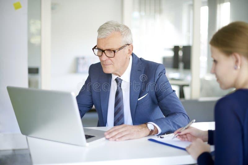 Consulente senior della banca sul lavoro immagini stock