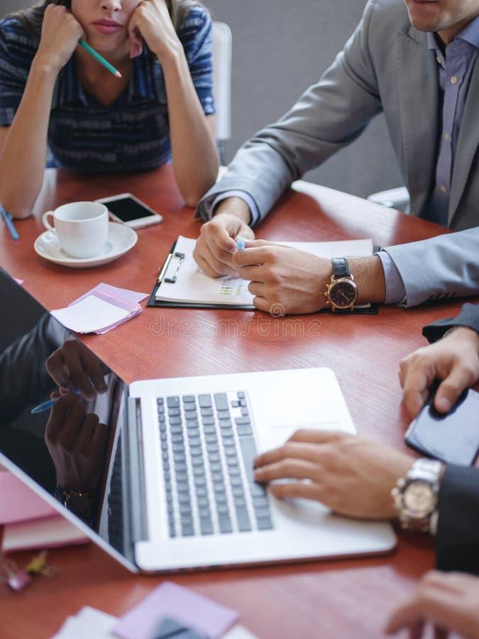 Consulenti in materia di affari mentre lavorando in un gruppo Un gruppo di giovani operai ad una riunione nell'auditorium della s immagini stock libere da diritti