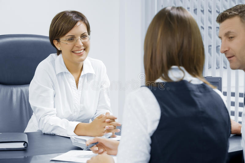 Consult. Portrait of young business people discussing project in office environment royalty free stock images