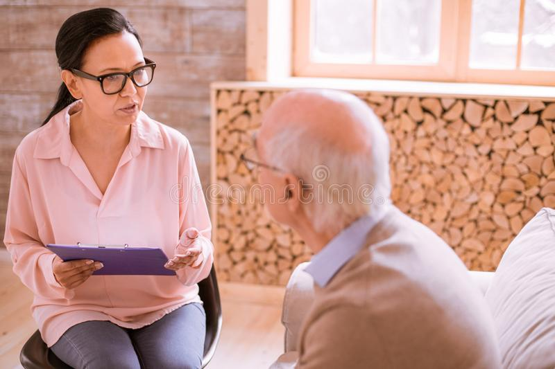 Attentive international woman working in nursing home stock photos