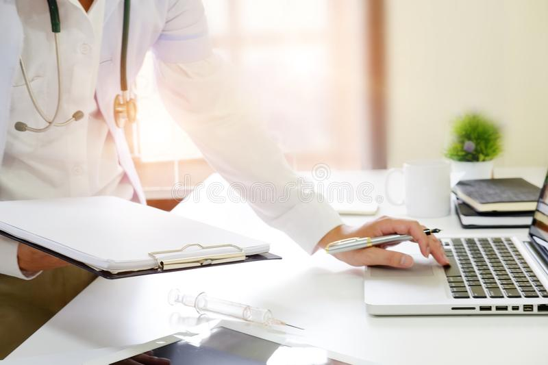 Consult medical , Close up doctor reading a report on workplace. royalty free stock photo