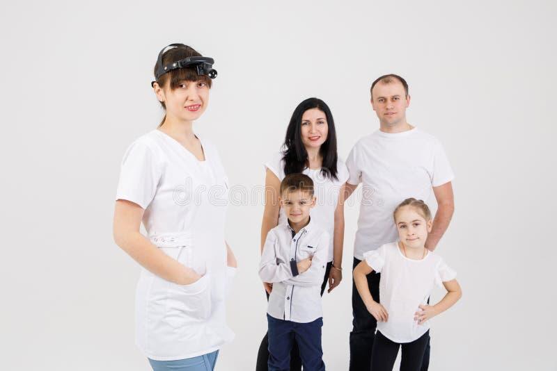 Consulta de un doctor y de los pacientes del otorrinolaring?logo - a?slan a los adultos y a los ni?os en un fondo blanco imágenes de archivo libres de regalías