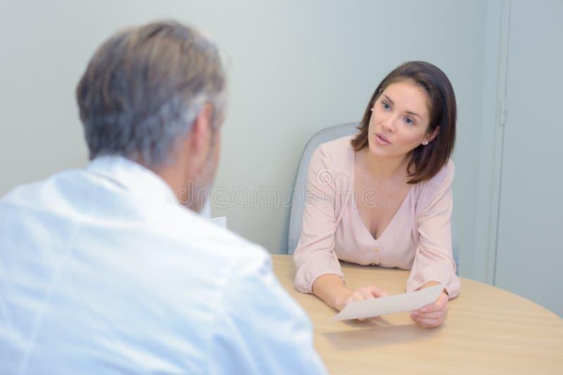 Consulta del doctor y del paciente durante examen médico en hospital imagenes de archivo