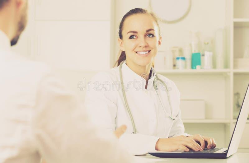 Consulta sonriente del doctor de la mujer imagenes de archivo