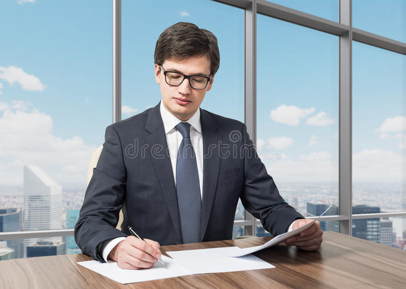 Consultant is dealing with due diligence process in a modern skyscraper office with a panoramic New York view. Handsome legal consultant is dealing with due royalty free stock image