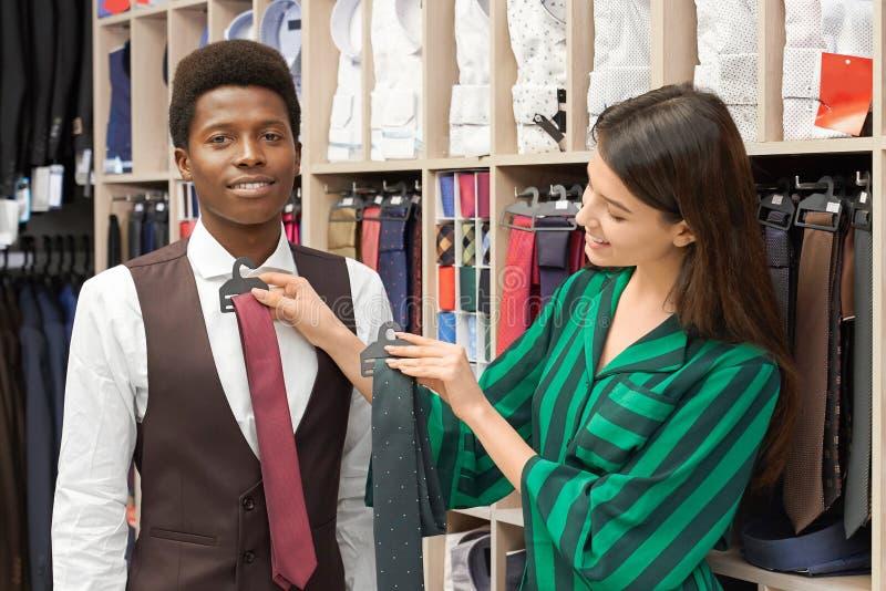 Consultant en matière de magasin essayant sur la cravate pour le client dans la boutique image stock