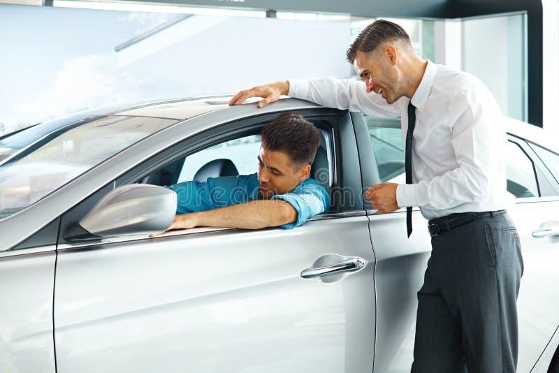 Consultant en matière Showing de ventes de voiture une nouvelle voiture à un acheteur potentiel dans S photo libre de droits