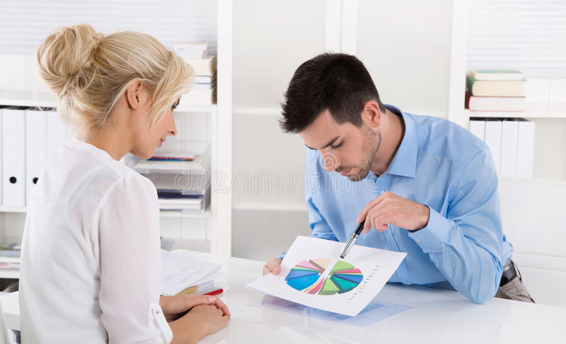 Consultant explain financial success to his customer with a graphic. stock photography