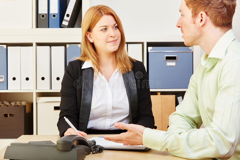 Consultant giving advice to a man. Tax consultant giving financial advice to a men in an office stock images
