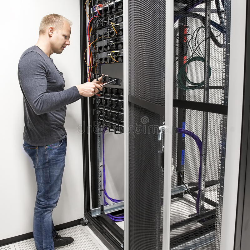 IT consultant install data racks in datacenter. IT engineer or technician working with network cabling and installation communication switches in datacenter stock photos