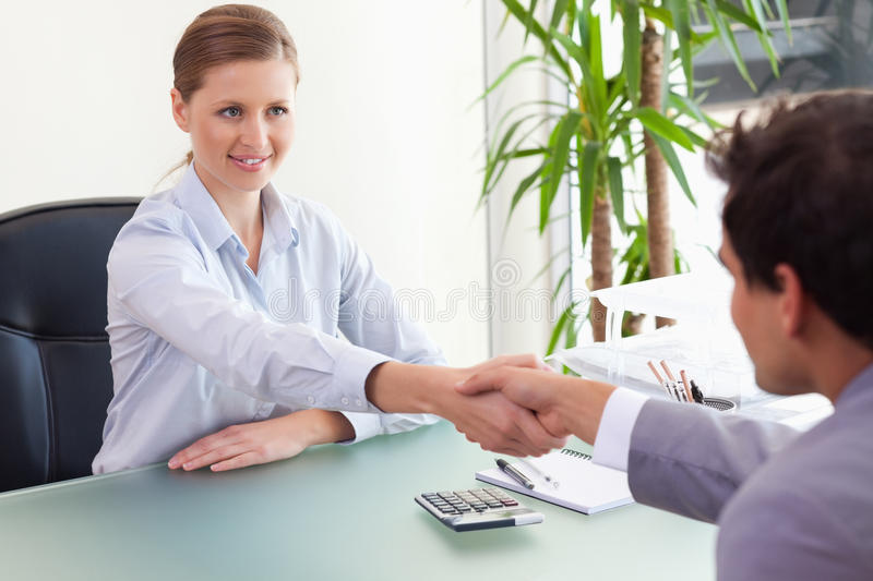 Consultant shaking hands with her client stock photos