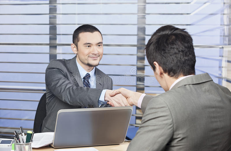 Consultant shaking hands with his client. Young consultant shaking hands with his client stock image