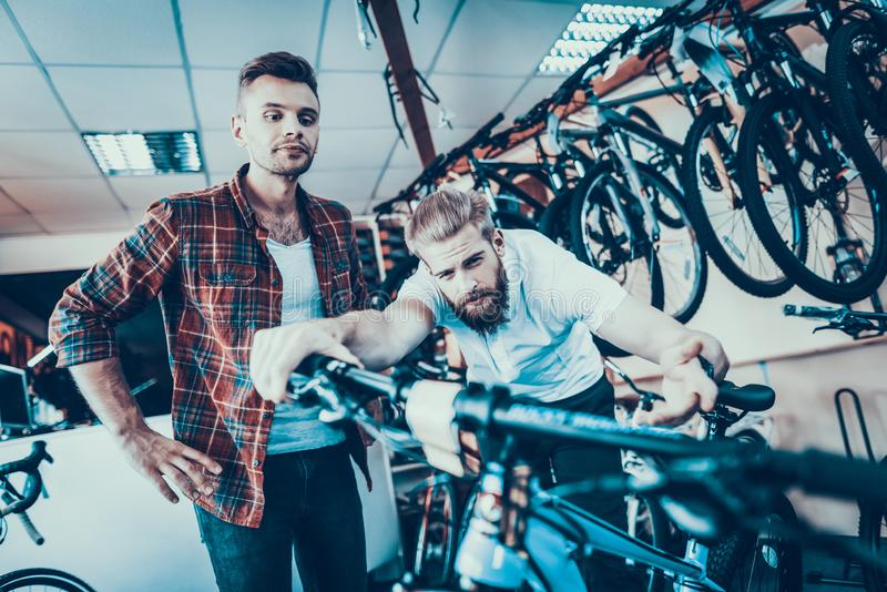 Consultant Shows Bicycle to Client in Sport Shop royalty free stock photo