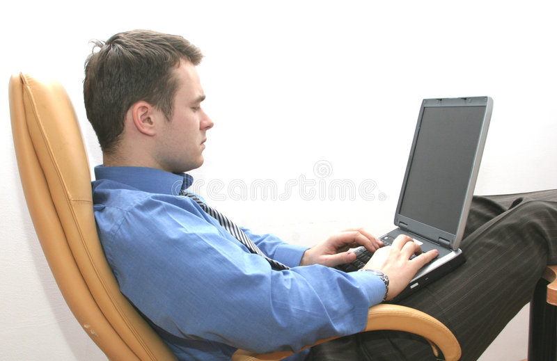 Consultant working on laptop. Consultant sitting in leather armchair in relaxed position and working on his laptop
