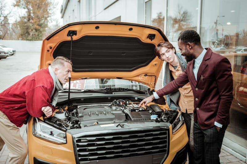Consultante afro-americano das vendas do carro que diz sobre o carro alaranjado fotos de stock royalty free