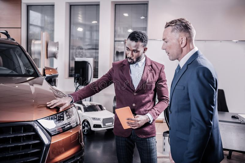 Consultante do salão de beleza do carro que diz sobre as vantagens do carro novo imagens de stock royalty free