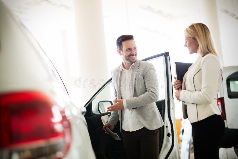 Consultante fêmea novo das vendas do carro que trabalha na sala de exposições fotografia de stock royalty free
