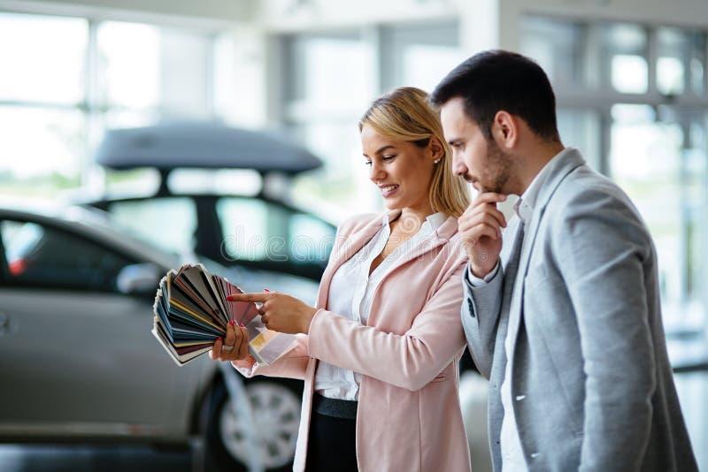 Consultante fêmea novo das vendas do carro que trabalha na sala de exposições imagem de stock royalty free