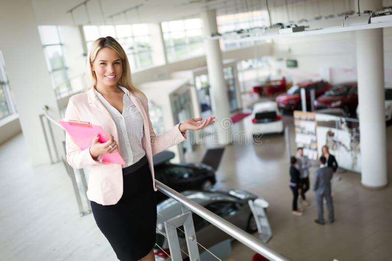 Consultante fêmea novo das vendas do carro que trabalha na sala de exposições foto de stock royalty free