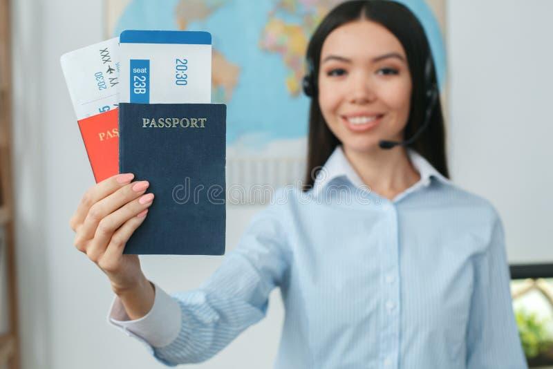 Consultante fêmea novo do agente de viagens na agência da excursão que guarda originais foto de stock royalty free