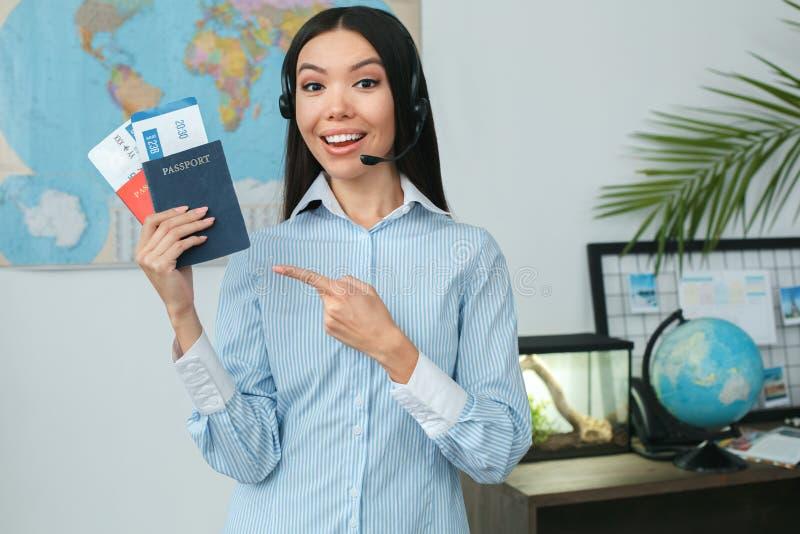 Consultante fêmea novo do agente de viagens na agência da excursão que mostra originais foto de stock royalty free