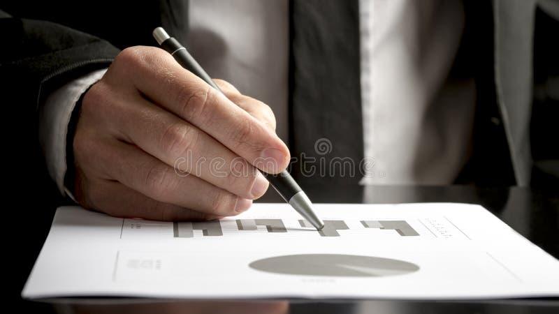 Consultante financeiro que revê gráficos e cartas estatísticos imagens de stock