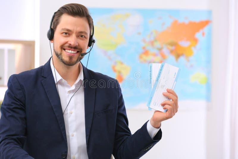 Consultante masculino com os auriculares que guardam bilhetes imagens de stock royalty free