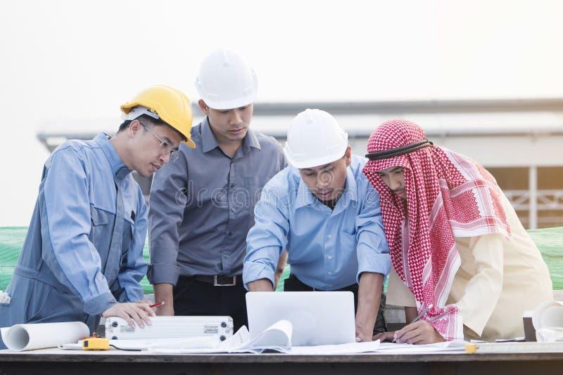 Consultaron juntos y planean a los ingenieros asiáticos en la construcción imagen de archivo libre de regalías