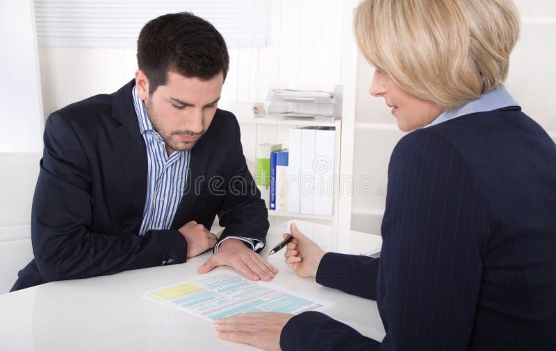 Consultation au bureau entre le conseiller et le client. images libres de droits