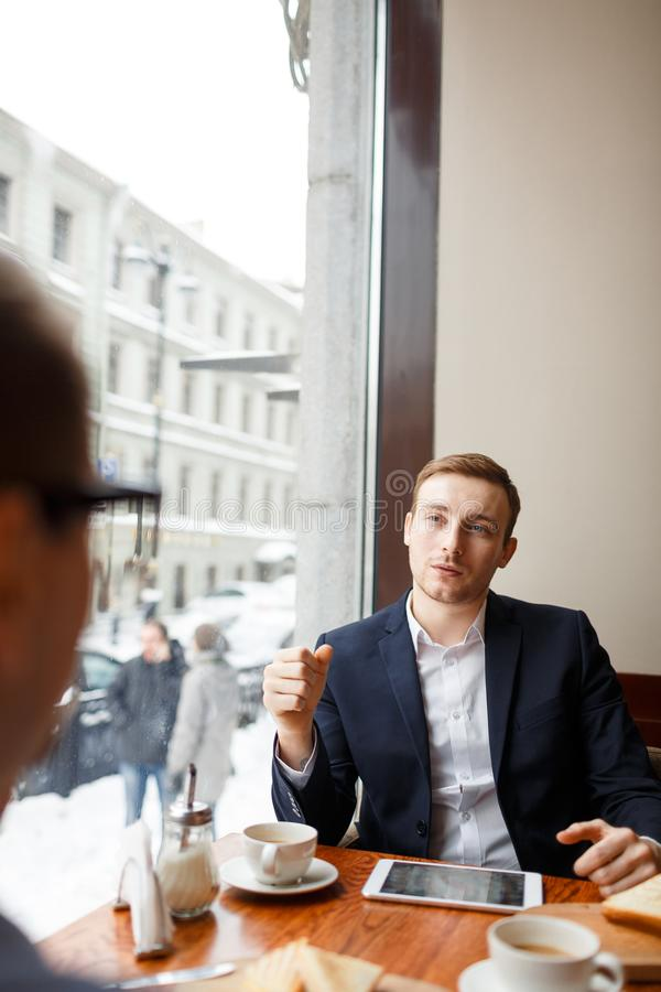 Consultation in cafe. Confident entrepreneur talking to business partner by cup of coffee in cafe stock photos