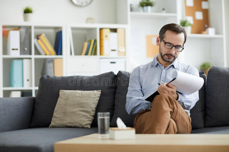 After consultation. Young professional counselor making notes in document while sitting on couch in his office after talk with client stock photography