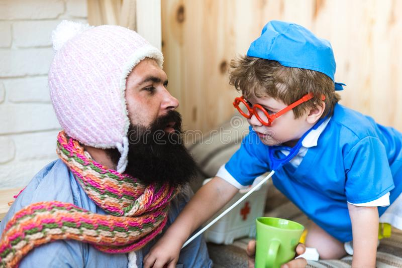 Consulting on the go. Son in glasses with stethoscope examine father at home. Little child play doctor with man. Medicine and health. Boy in doctor uniform royalty free stock photography
