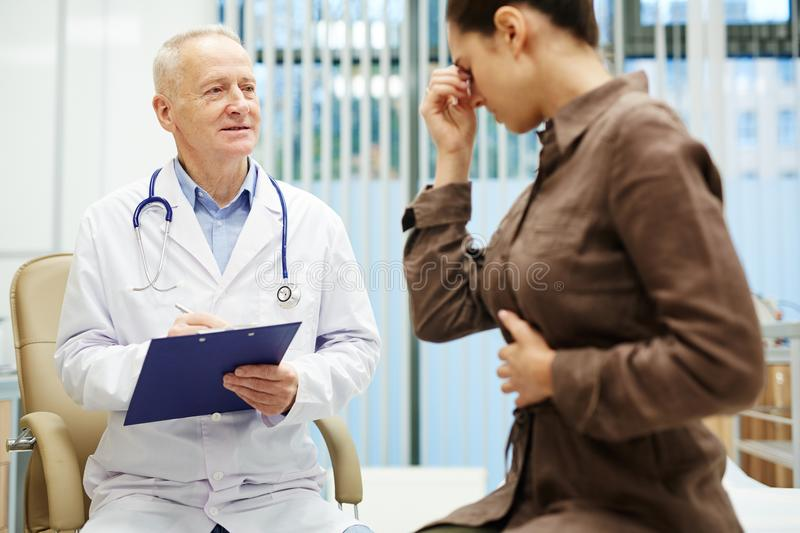 Consulting patient. Confident senior doctor consulting young sick patient and making prescriptions stock images