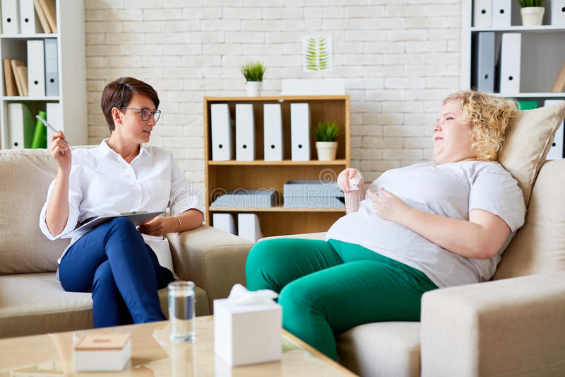 Consulting patient. Experienced psychologist talking to her patient with overweight royalty free stock photography