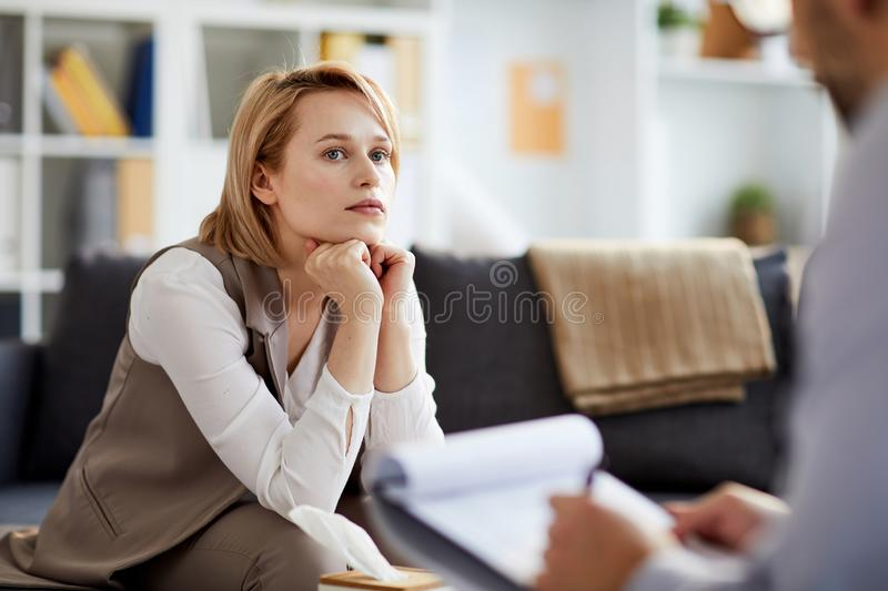 Consulting psychologist. Young serious and concentrted women listening to her counselor while sitting on couch during consultation stock photo