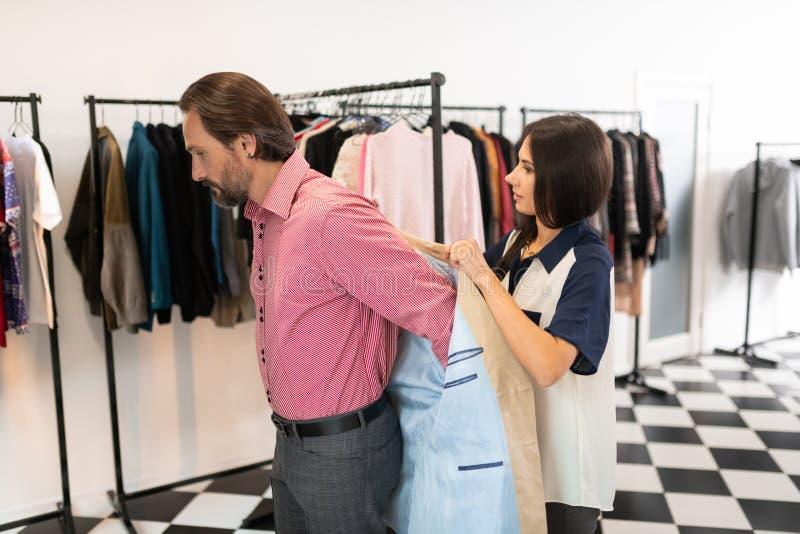 Consultor bueno que ayuda a un cliente durante intentar en una chaqueta foto de archivo