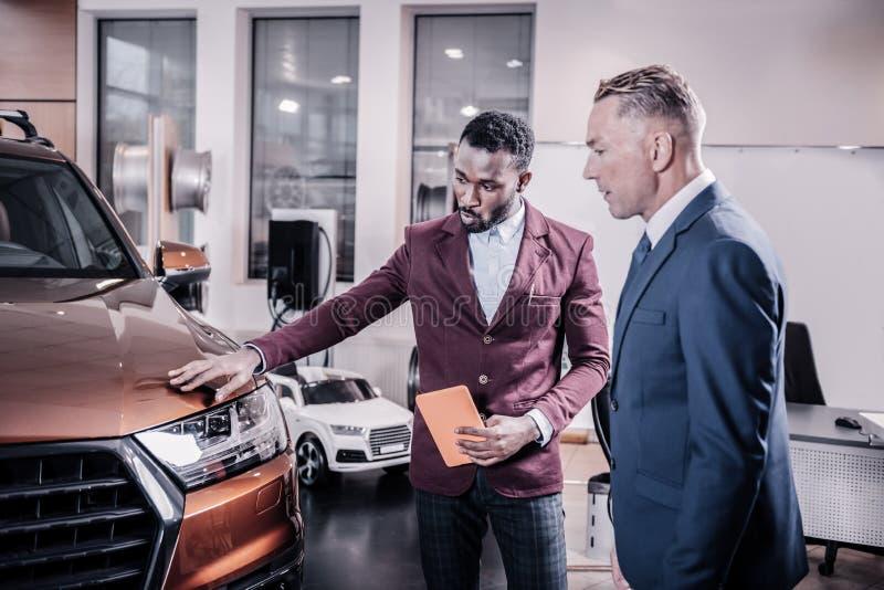 Consultor del salón del coche que habla de las ventajas del nuevo coche imágenes de archivo libres de regalías
